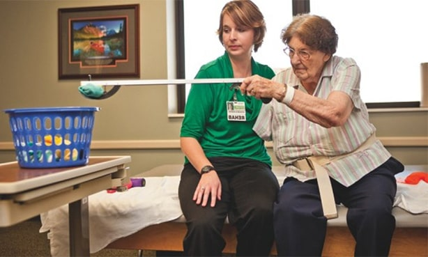 Реабилитолог работает с парализованной рукой