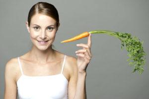 Девушка держит морковь в руке