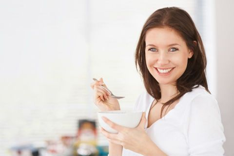 Женщина завтракает кашей