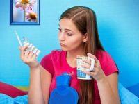 Девушка с градусником, таблетками и грелкой